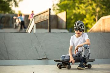 Boy posing with his skateboard at skate park