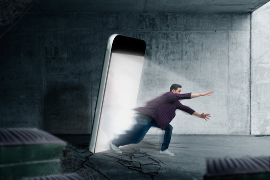 Man jumps out from a glowing smartphone screen