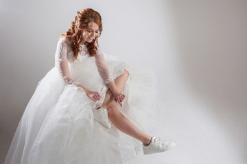 Runaway bride laces shoelaces. girl in a magnificent wedding dress and white sneakers