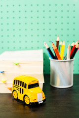 Back to school supplies pastel workspace with pencils, Books, toy school bus
