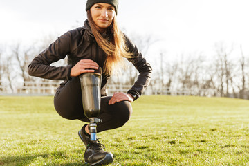 Image of young handicapped sportswoman in tracksuit, squatting and touching bionic leg outside