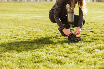 Cropped image of handicapped sportswoman in tracksuit, squatting and tying shoelaces on prosthesis leg outside