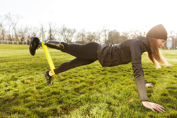 Image of sporty handicapped woman in black tracksuit, warming up and doing plank with prosthesis leg on nature using rubber band