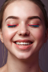 Beauty portrait of cheerful woman with colorful make-up. Blue eyelashes and pink eyeliner