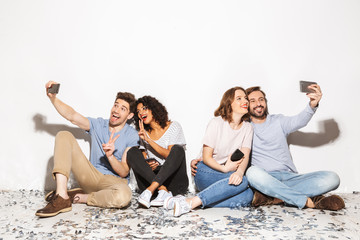 Group of happy multiracial people sitting on a floor