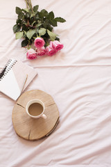 Coffee, pink roses, notebooks in bed on pink sheets. Freelance fashion home femininity workspace in flat lay style