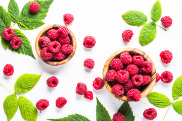 Fresh raspberries in wooden bowl on white table.