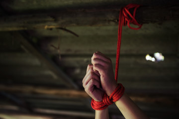 Closeup hostage hands tied by red rope