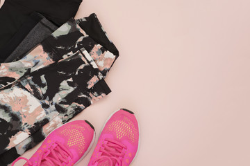 Female pink sneakers, sport shoes, leggings in flat lay style, top view. Fitness concept, active lifestyle, body care concept. Copy space