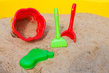 children's sandbox and colorful plastic toys pail bucket and rake for playing outdoors in the summer day concept of development and recreation of children with copy space