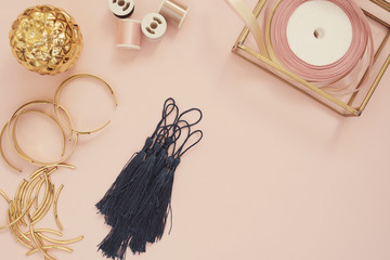 Jewelry designer workplace. Handmade, craft concept. Materials for making jewelry ? golden scissors, ribbons, gold tubes, bracelet settings, tassels. Freelance workspace in flat lay style.