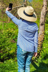 Woman in straw hat take selfie in garden