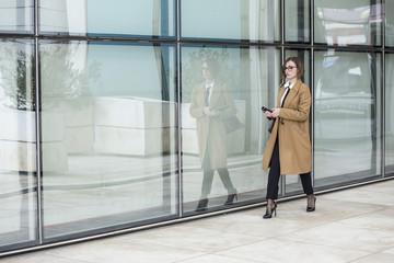 Donna d'affari con occhiali da vista vestita con cappotto beige , camicia  bianca e cravatta nera , cammina lungo una parete di vetro in cui si riflette