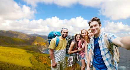 technology, travel, tourism, hike and people concept - group of smiling friends with backpacks taking selfie over big sur coast of california background