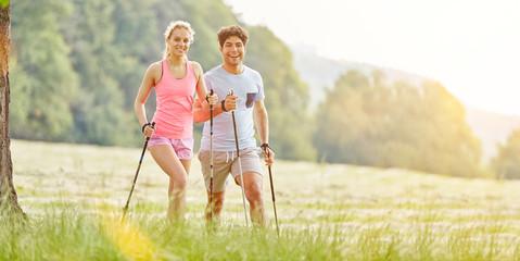 Paar beim Nordic Walking im Sommer