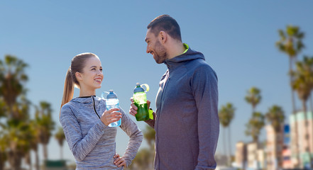 fitness, sport and people concept - smiling couple with bottles of water over venice beach background in california