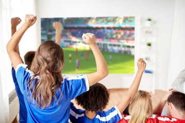 sport, leisure and entertainment concept - happy friends or football fans watching soccer on projector screen at home and celebrating victory