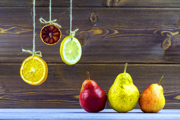 Hanging on ropes slices of lemon, orange and lime. On the table lay a ripe pears