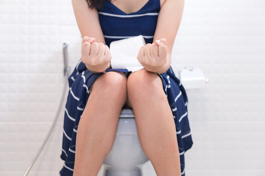 Woman sitting on toilet with toilet paper - constipation concept.