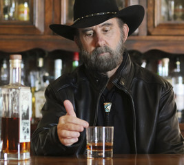 A Bearded Cowboy in Black Sitting Alone in a Saloon