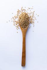 Fotobehang Zonnebloem Spoon full of sesame grains on white background