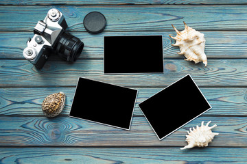 camera, seashells, photos with black filling, on a wooden background of blue color. travel, cruise.