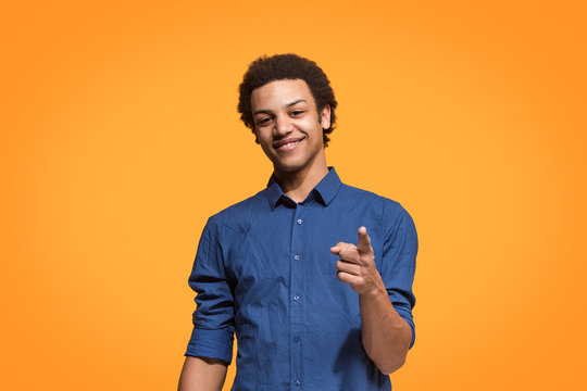The happy business man point you and want you, half length closeup portrait on orange background.