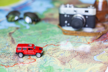 Car, glasses and camera on the world map