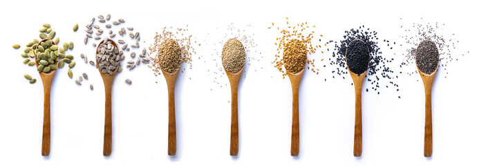 Set of spoons with different seeds on white background