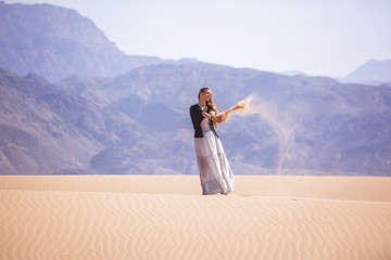 Woman standing on a sand dune in the desert of Jordan