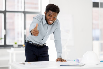 architecture, construction business and people concept - smiling african american architect with blueprint working at office and showing thumbs up