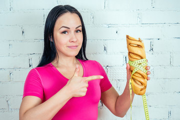 portrait of a beautiful and young woman looking at a baked high-calorie bread loaf with a yellow measuring tape on a white brick wall background in the gym. fitness concept and diet