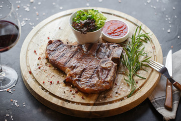 Grilled steak served on wooden board. Top view