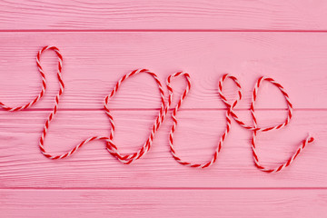 Word love written with woollen thread. Text love on pink wooden background. Love and romance concept.