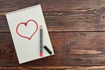 Red pencil and a drawn heart. Paper notebook with image of red heart, pencil and copy space. Beauty and love.