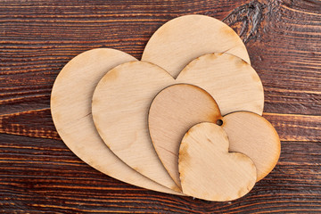 Collection of plywood hearts for decoupage. Wooden heart tags on brown wooden table, top view.