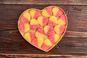 Jelly candies in heart shaped box. Colorful heart-shaped jelly sugar candies in a heart-shaped box on a brown wooden table, top view.