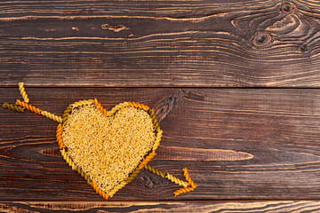 Valentines Day wooden background. Top view of heart with an arrow made of pasta and copy space.