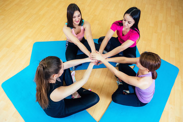 a group of four women meditate on mats in the gym. concept of group yoga therapy female support