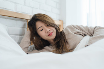 Portrait beautiful young Asian woman on bed at home in the morning. Cheerful Asian woman wearing a comfortable sweater and smiling on her bed. Relaxing room. lifestyle asia woman at home concept.