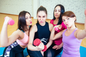 four beautiful and young women girlfriends are photographed selfie on the phone in sportswear in the gym. group portrait of a woman selfie having fun with dumbbells
