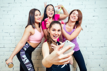 four beautiful and young women taking pictures on the phone in sports clothes in the gym. girlfriends woman do selfie in sportswear