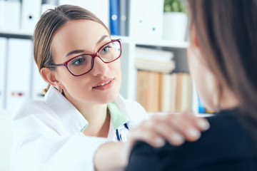 Friendly female doctor in glasses touching patient shoulder. Encouragement, empathy, cheering and support after medical examination.