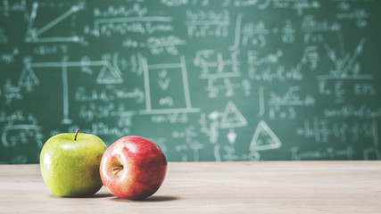Back to school concept with apples in front of green chalk board