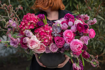 The florist holds beautiful composition of flowers in basket