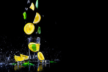 Lemonade with flying lemon and mint, isolated on a black background, free space.