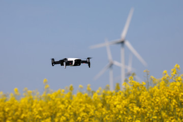 Mini drone floating above rapeseed field surveilling the wind turbines, recording videos and taking pictures. New and modern guardian of big companies. Blurred background