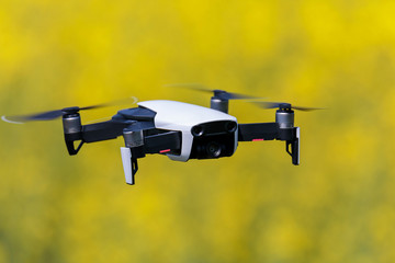 mini drone floating above rapeseed yellow field recording videos and taking pictures