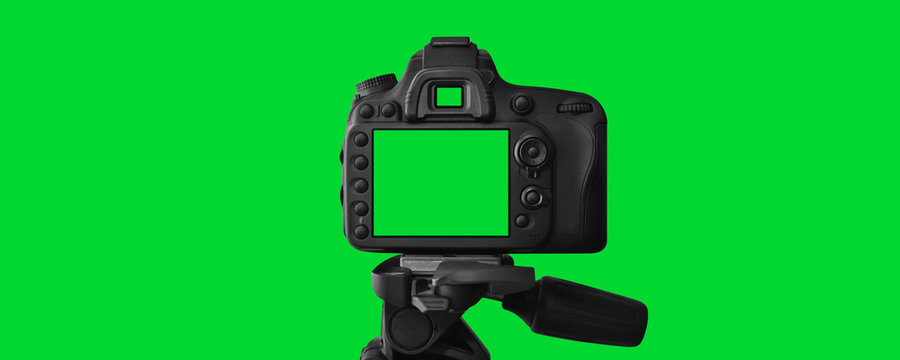 The Dslr camera with empty screen on the tripod, isolated on green background. The chromakey. Green screen.
