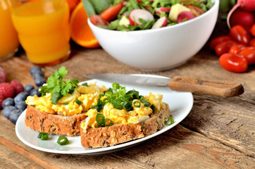 Wholemeal bread with scrambled eggs, fresh herbs, spring onions, orange juice, tomatoes and salad bowl in background